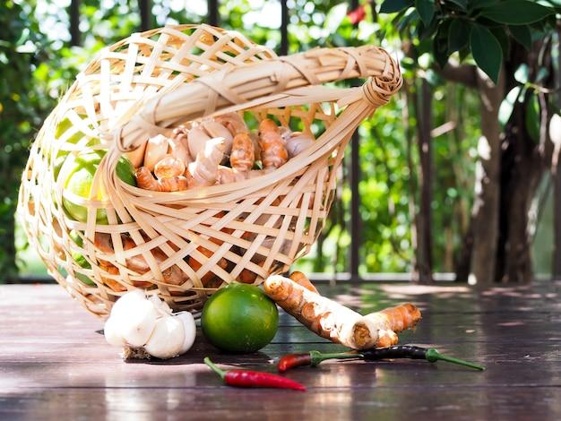 タイのキッチンで野菜と手作りの枝編み細工品セットレモン、ウコン根、ニンニク、唐辛子、生ingerの木製テーブルの上。
