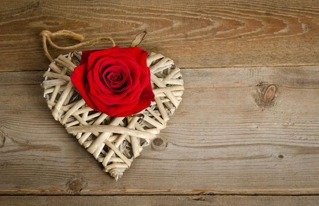 Handmade wicker heart with bud of red rose