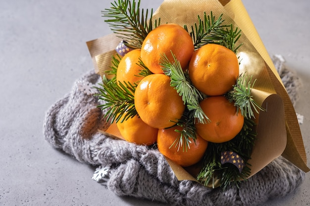 Handmade winter fruit bouquet of mandarin and christmas tree branches