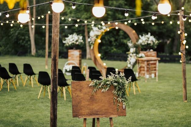 緑の植物で飾られたウェルカムサインのための手作りの木の板。ボードガーデンでのレセプションでのウェディングへようこそ