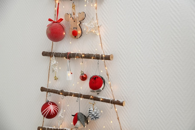 Handmade wooden christmas tree with toys hanging on the wall