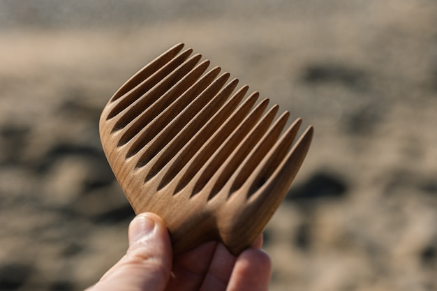 Handmade wooden comb for hair care in man hand