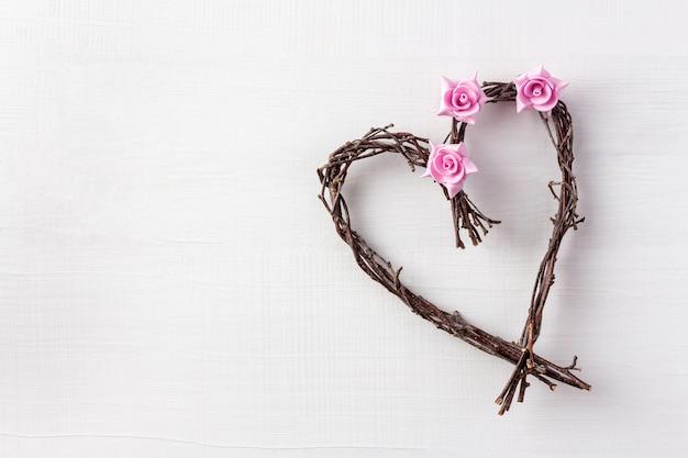Деревянное сердце ручной работы с цветами на день святого валентина на белом фоне