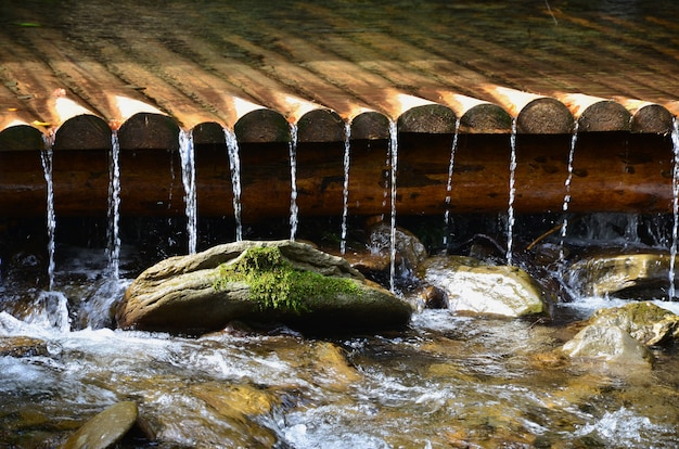 Handmade wooden water drains from small treated beams. a beautiful fragment of a small waterfall