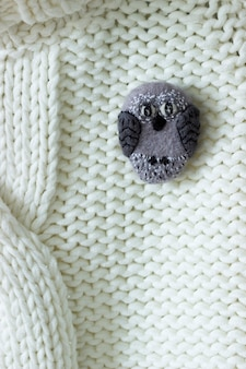 Handmade wool brooch on a sweater background. selective focus, rustic style.