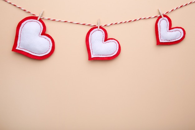 Handmaded hearts on a rope on beige background.
