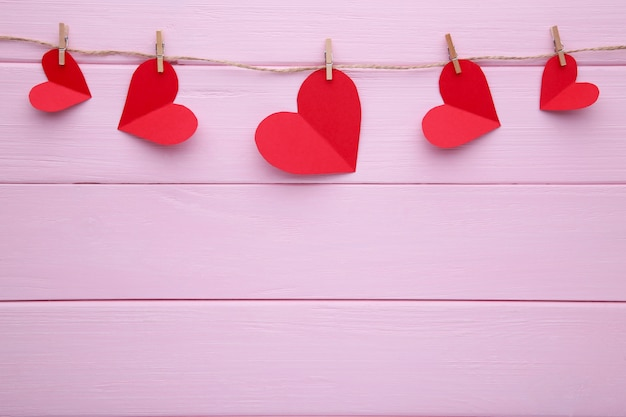 Handmaded hearts on a rope on pink background.