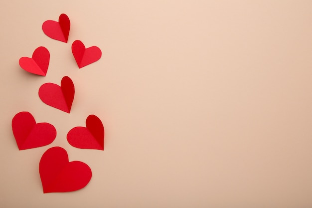 Handmaded red hearts on beige background.