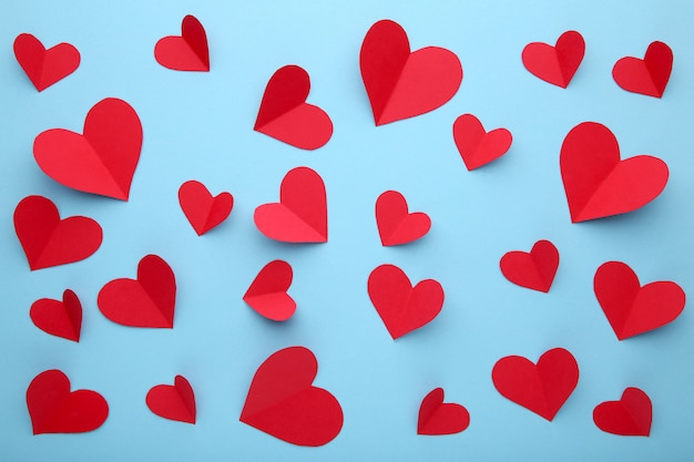 Handmaded red hearts on blue background.