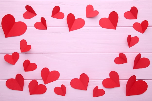 Handmaded red hearts on pink background.