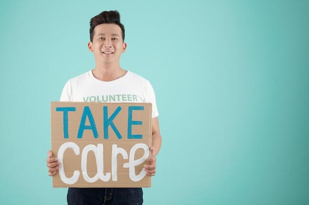 Молодой азиатский доброволец handosme держит картонный плакат с надписью `` береги себя '' и улыбается в камеру