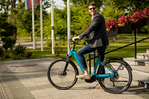 Handosme young businessman on the ebike at the street