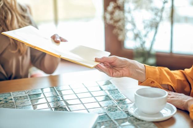 引き渡す。クライアントに書類を渡す女性の手のクローズアップ
