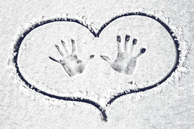 Handprints on the snow circled in heart, background