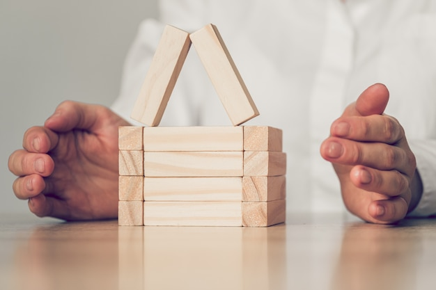 Hands abstractly protect a house from wooden blocks