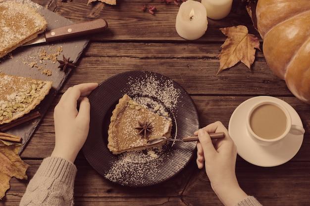 손과 나무 테이블에 호박 파이