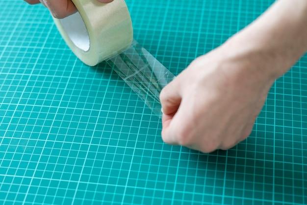 Руки, наклеивающие скотч на поверхность
