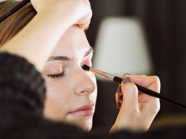 Руки, применяя макияж глаз крупным планом