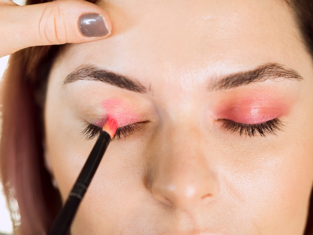 Hands applying eyeshadow front view