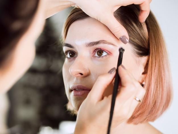 Руки наносят макияж на милую модель