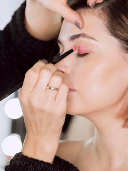 Руки нанесения макияжа на модель
