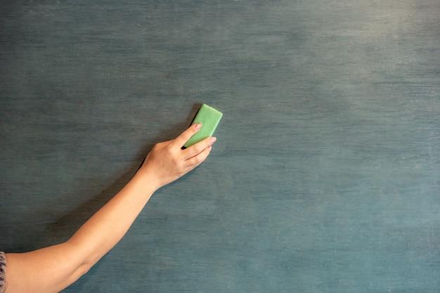Hands are erasing the blackboard