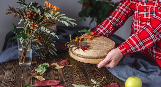 В руках муссовый коричневый торт, украшенный осенними листьями и ягодами.
