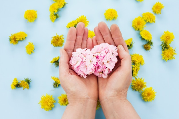 手はパステルブルーのスペースに明るい花を持っています。