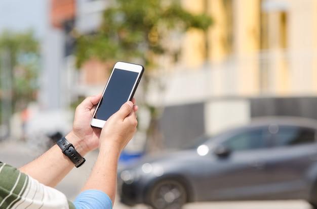 손이 흐릿한 건물과 자동차 배경에 터치 스크린 스마트 폰을 들고 있습니다.