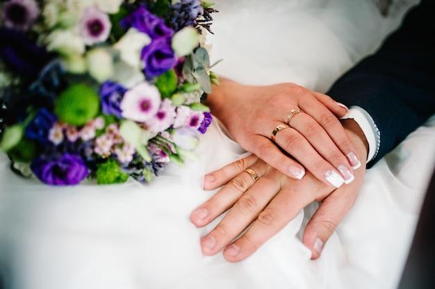 손은 결혼 반지를 가진 신혼 부부입니다. 확대. 꽃의 웨딩 부케의 배경. 신부 매니큐어. 신랑