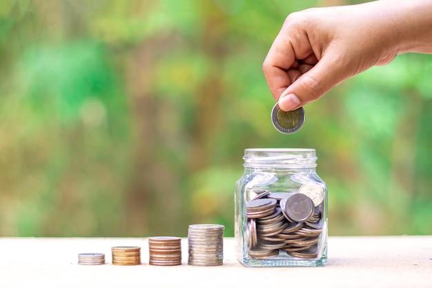 手は自然な緑のぼかしの背景にボトルにお金を入れています。お金を節約するためのコンセプト。