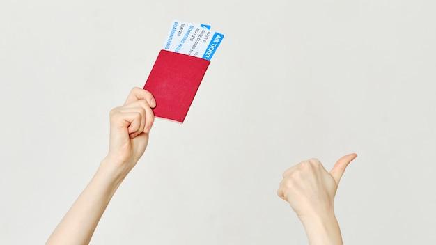 手を挙げて、パスポートと飛行機のチケットを持ち、親指を立てます。