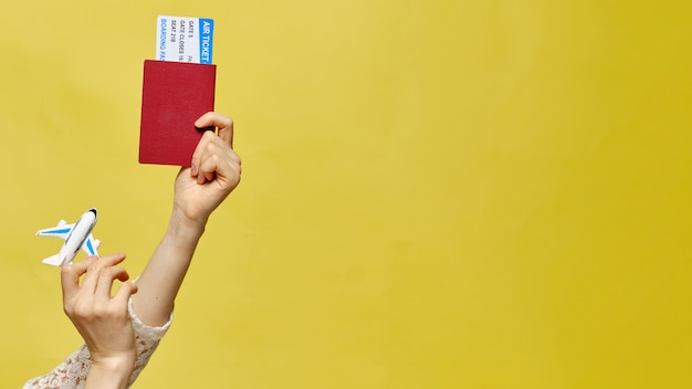 Hands are raised up and holding tickets with a passport toy airplane on a yellow background. copy space.