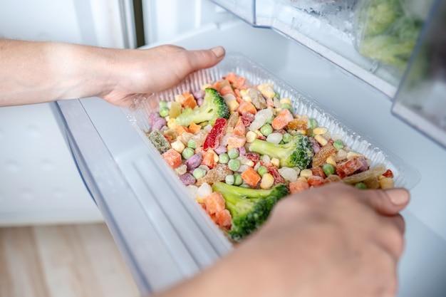 手は冷蔵庫の冷凍庫から冷凍野菜の容器を取っています