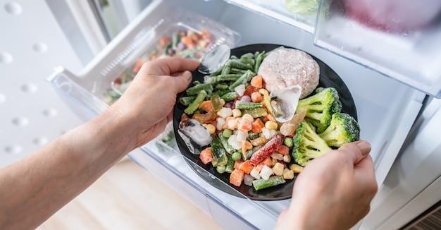 手は冷蔵庫の冷凍庫から冷凍食品のプレートを取り出しています Premium写真
