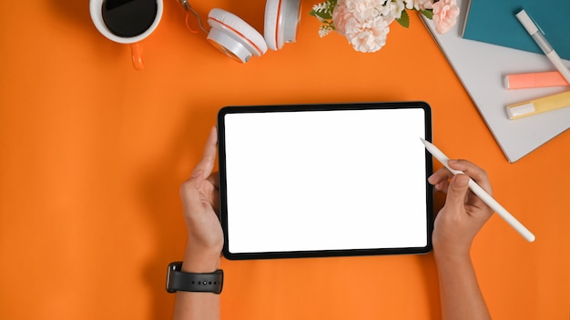 Hands are using a white blank screen computer tablet and stylus pen on a colorful table