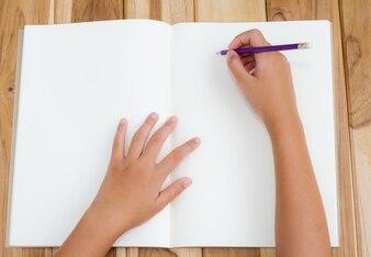 手は木製の床の手帳に書いている