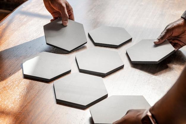 Руки раскладывают связанные бумаги с вырезом из шестиугольника