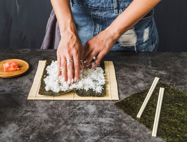 Hands arranging ingredients on sushi mat
