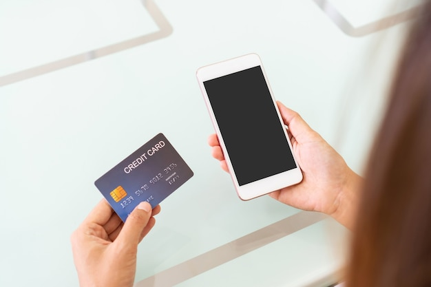 Hands of asian woman using mobile phone with blank screen for copy space, advertisement while holding credit card in cafe. top view. technology and lifestyle concept.