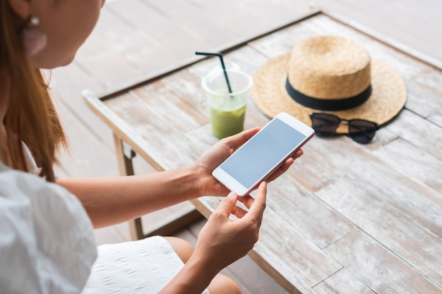 Hands of asian woman using smart phone with iced matcha latte, hat, sunglasses on wooden table in cafe. closeup. relax on weekend concept.
