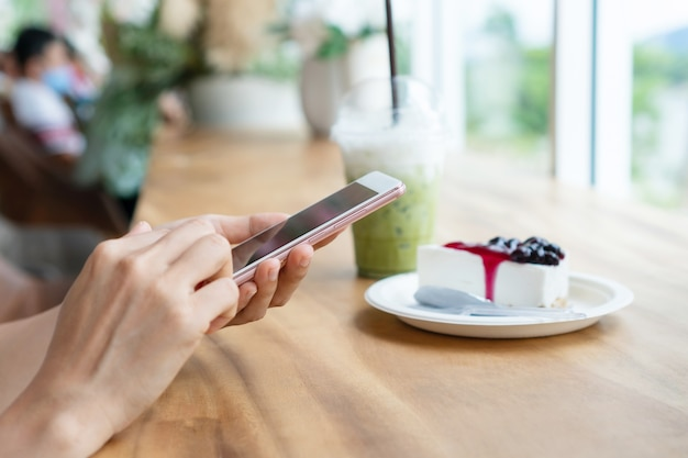 Hands of asian woman using smart phone with iced matcha latte on wooden table in cafe.