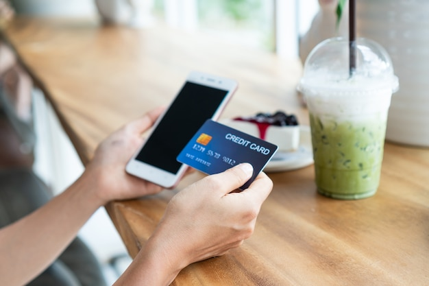 Hands of asian woman using smartphone while holding credit card on wooden table in cafe. closeup, copy space. shopping online, business and technology concept