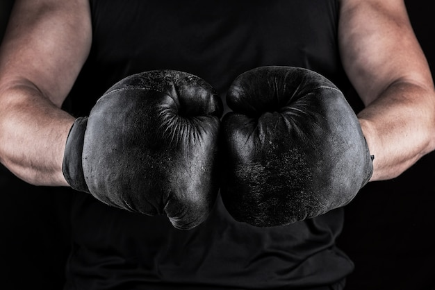 Hands of an athlete in black old sport boxing gloves