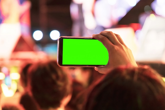 Hands of audience crowd people taking photo with mobile smart phone with green screen in party concert.