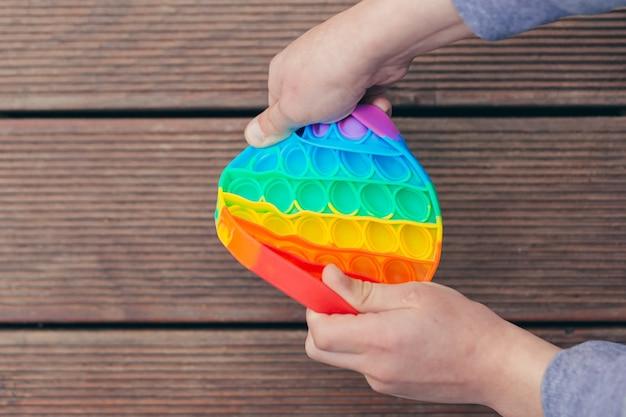 Руки мальчик подросток играет в антистрессовую игру поп на открытом воздухе