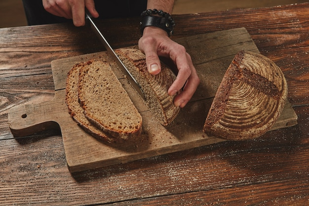 茶色の木製の机の上でライ麦パンを切るハンズベーカリー