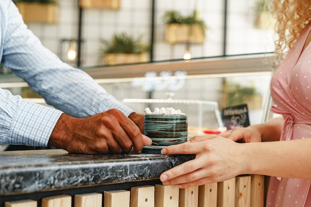 Hands of barista serving a cup of hot cocoa drink decorated with marshmellows on counter