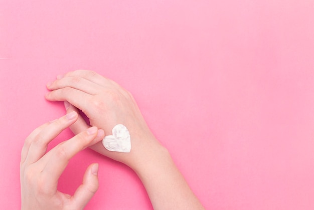 Hands of a beautiful well-groomed woman with a cream jar on a pink textural background.
