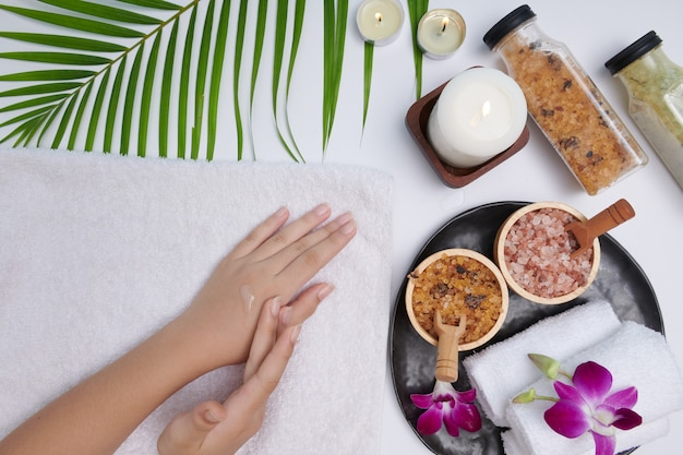 Hands of a beautiful woman dropping pine essential oil. spa treatment and product for female hand spa, massage, candles, relaxation. flat lay. top view.